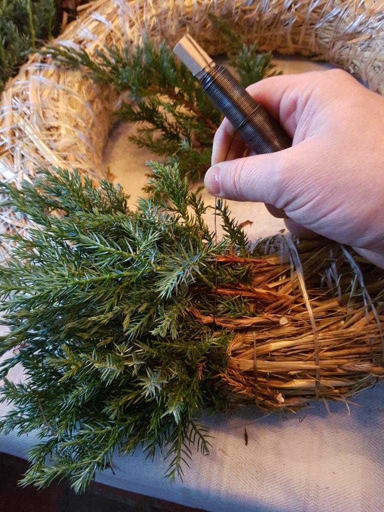 Puslespillet starter med å legge de små avklipte grenene lagvis for å dekke hele bredden. Ta et par runder med vikletråden og stram godt!